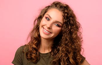 Attractive young woman with curly hair and pretty smile wearing dental braces.