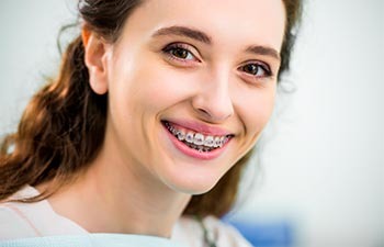 A smiling woman with orthodontic braces on teeth.
