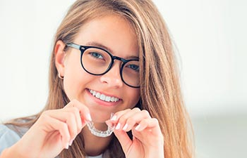 Young smiling girl holding clear orthodontic aligner.