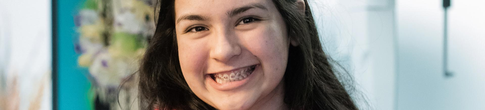 A cheerful teenage girl with orthodontic braces.