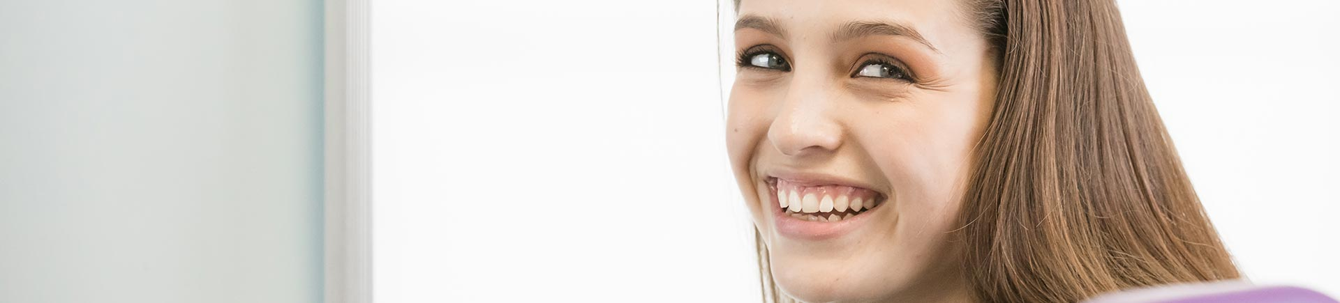 Satisfied teenage girl with perfect smile after orthodontic treatment.