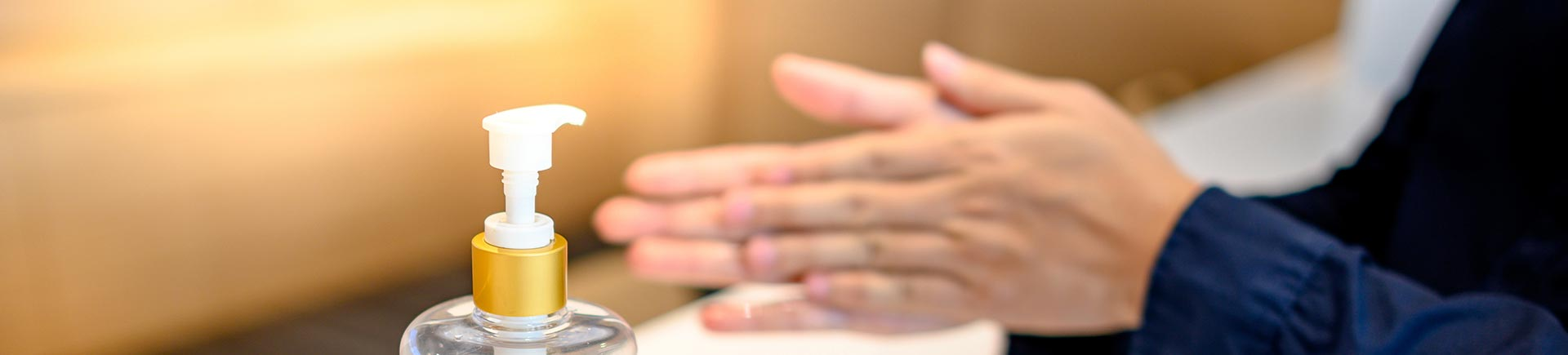 Washing hands with alcohol sanitizers or alcohol gel from pump bottle.